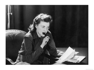 Woman Sits with Her Pen in Her Mouth Whilst Thinking About What She Should Write in Her Letter