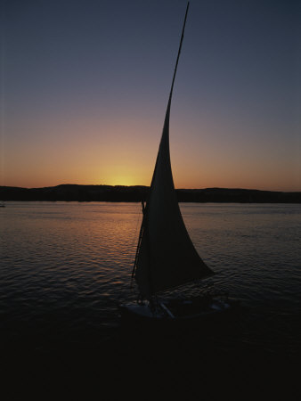 Sunset Outlines the Curve of a Felucca Sail on the Nile River