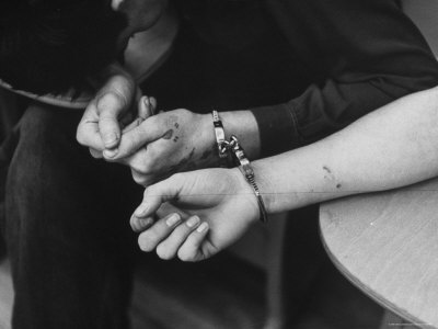 Close Up of Handcuffs, One Woman's Arm to a Man's During a Round Up of Dope Addicts