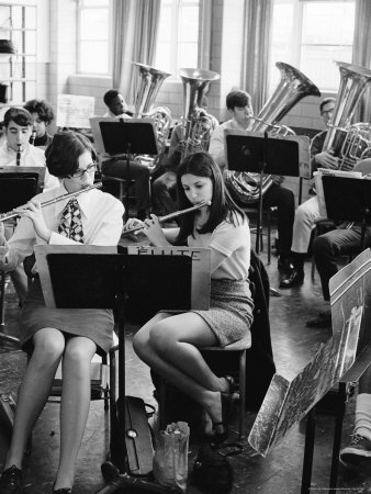 Black and white photograph, teen girls in front row with flutes, boys in back with brass instruments