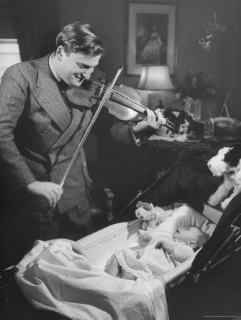 black and white photograph of Yehudi Menuhin at left, looking down at his daughter in her crib, wrapped in a blanket, and playing violin. Behind him are a dresser, lamps, and a painting on the wall.