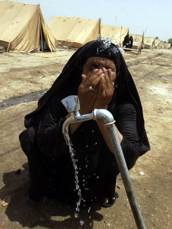 A Woman Washes Her Face with Water from a Tap at a Camp for Displaced Iraqis