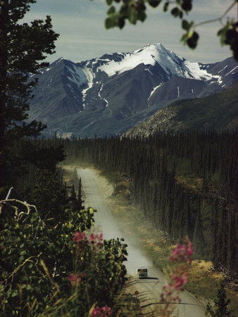 A Camper Rolls Down a Dirt Road Below High Mountains in Alaska Photographic Print