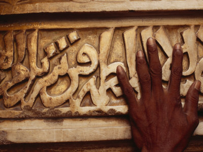 A Man Runs His Hand Over Arabic Script at the Famous Jama Masjid