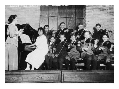 black and white photograph. Woman in suit with long skirt leads orchestra of older children