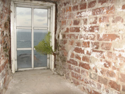 Weathered and Worn Brick Walls and Rustic Window Overlooking Ocean