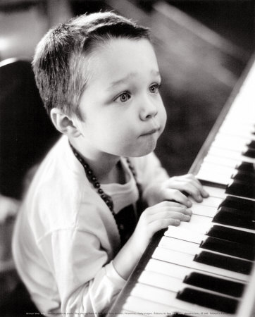 Black and white photograph of young boy with worried expression playing the piano