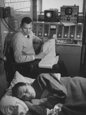 Black and white photograph of man in white shirt, tie, dark pants, and light v-neck sweater, holding an EEG printout and his reading glasses,  watches a man in pajamas sleeping with his face turned towards the viewer. Behind them is a bank of computers.