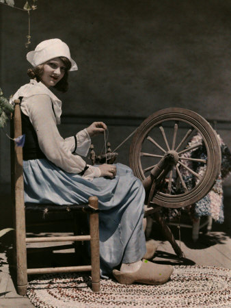 Girl Sits Spinning Cotton into Yarn in Preparation for Cloth