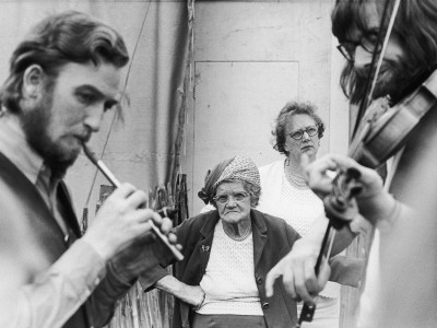 black and white photograph of two bearded men indoors; man on left plays pennywhistle, man on right plays violin; in the background two casually dressed older women look on.