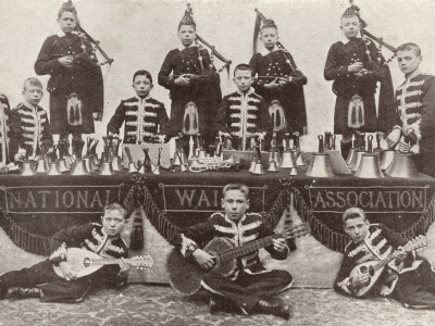 "Back row: four boys with bagpiper in piper costume. Middle row: Four boys with handbells. Front row, left and right, boys with gourd mandolin, reclining; center, seated boy with small-sized guitar. Bunting reads ""National Waifs Association"""