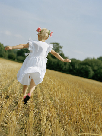 A Little Girl in a White Summer Dress, Running in a Field
