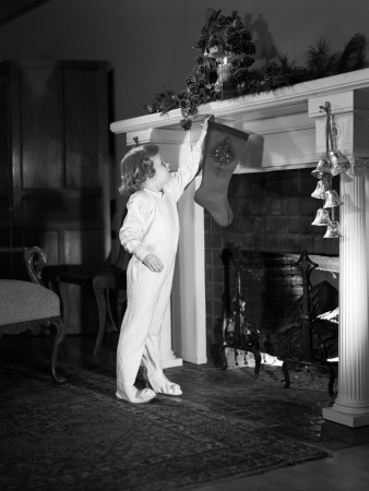 Young Girl in Full Body Pajama Suit Hanging Christmas Stocking Over Fireplace
