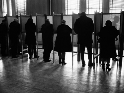 Men and Women Standing Side By Side in Voting Booths, Filling Out Election Ballots