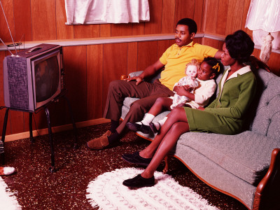 Parents and Young Daughter Sitting in Living Room, Watching Television