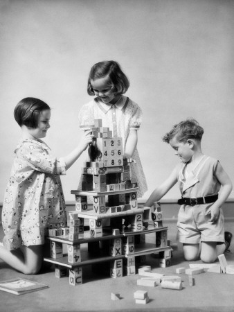 Two Girls and One Boy Playing With Alphabet Building Blocks