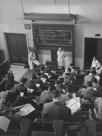 black and white photograph of teachers in lab coats standing in front of blackboard with writing; male students in suits studying and taking notes