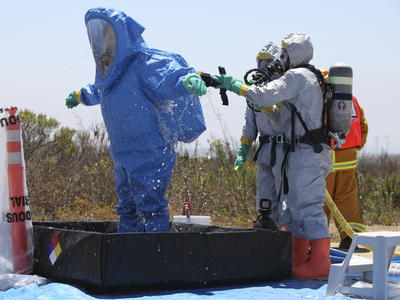An Airman Stands in a Tub of Cleaning Solution During a Decontamination Process