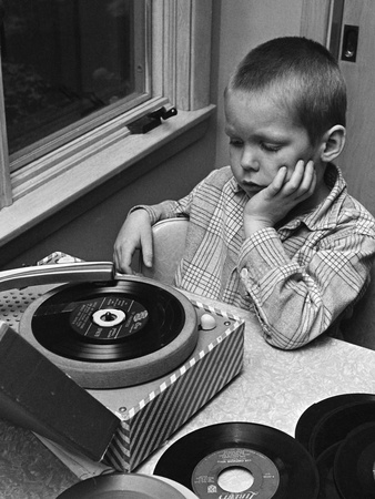 Black and white photograph of unhappy-looking boy in plaid shirt listens to 45-rpm record on an inexpensive record player at a table next to a window; more 45-rpm records are piled on the table