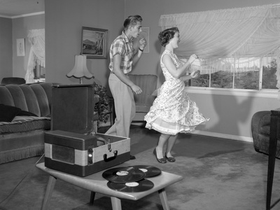 1950s Laughing Teenage Couple Dancing To The Phonograph Playing 78 Rpm Records In Living Room..