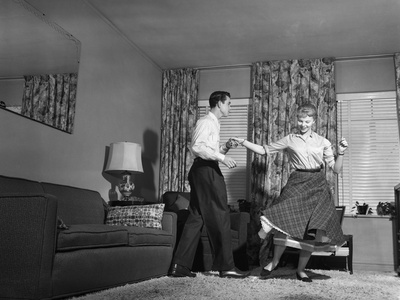 1950s Teen Couple Doing Jitterbug Rock And Roll Dance In Living Room Man Woman Boy Girl..