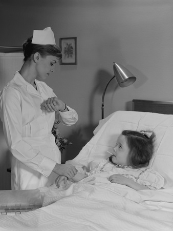 Black and white photograph of a woman in white nurse's uniform with cap and hair in a bun looks at her watch. A girl lies on a hospital bed with a thermometer in her mouth; the woman is holding the girl's wrist