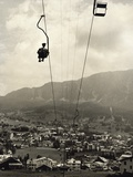 Man Riding Chair Lift Above Town