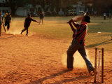 Cricket Batsman Swings on Dusty Pitch, Fort Cochin, India