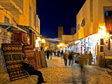 People Strolling along Cobblestone Street Past Carpet Seller at Twilight, Kairouan, Tunisia