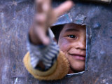 Boy Reaching through Hole in Gate, Alchi, Jammu and Kashmir, India