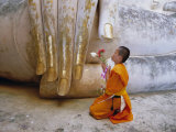Novice Buddhist Monk Kneeling Beneath the Phra Atchana Buddha Statue, Sukhothai Province, Thailand