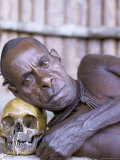 Portrait of an Asmat Tribesman Leaning on a Human Skull, Irian Jaya, Indonesia
