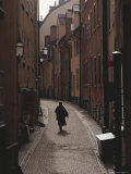 Sweden, Stockholm, Woman Walking on Narrow Streets of Gamlestaden, Rear View