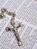 Silver Crucifix Lying on Open Bible