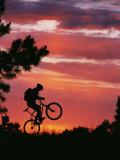 Silhouetted Biker Pulls a Wheelie at Twilight