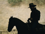 A Silhouette of a Rancher Riding a Horse