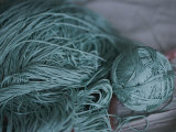 A Ball of Green Silk Yarn Lies Near a Pile of Unwound Yarn
