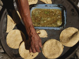 A Vendor Displays a Sample of Local Mexican Cooking with Tortillas