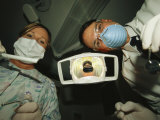 A Dentist and Dental Hygienist Prepare for an Examination