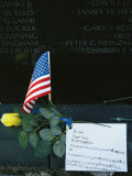 Rose, Flag, and Note of Remembrance Left by a Family at Memorial Wall