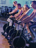 Group of People on Exercise Bikes in a Health Club