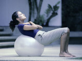Side Profile of a Young Woman Exercising on a Fitness Ball