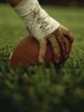 Close-up of the Hand of an American Football Player Holding a Football