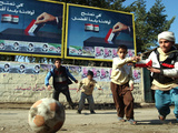 Iraqi Boys Play Soccer Below the Poster Reading 