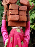 An Indian Woman Construction Worker Stacks Bricks on Her Head