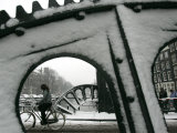 A Cyclist Passes a Draw Bridge as Snow Covers the City Center of Amsterdam