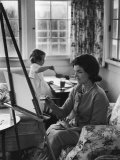 Jackie Kennedy, Wife of Sen, Painting on an easel as Daughter Caroline Paints on Table at Home
