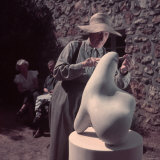 French Sculptor Jean Arp, Alone, Polishing Abstract Sculpture in His Garden Near Paris