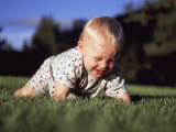 A Baby Boy Crawls Through the Green Grass