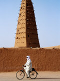 Robed Tuareg Man Cycling Past Minaret of Mud-Brick Grande Mosquee, Agadez, Niger